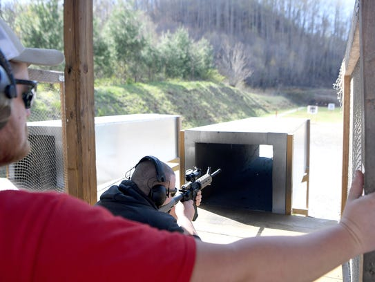 Aaron Jones, a range officer, watches as Javier Moraga