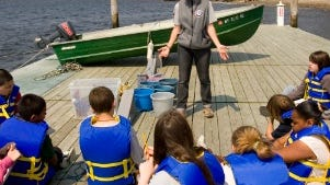 Americorps volunteer Krista Cole, center, talks with sixth grade students from Park View Middle School during a marine biology and ecology session at Narragansett Bay.