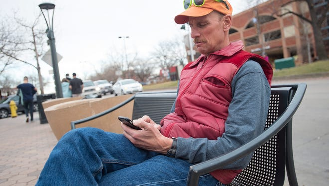 Jonathan Zeif browses his phone in Old Town Fort Collins on Saturday, March 24, 2018. The town of Timnath launched an online petition recently to document complaints and issues with Verizon Wireless service in the area.