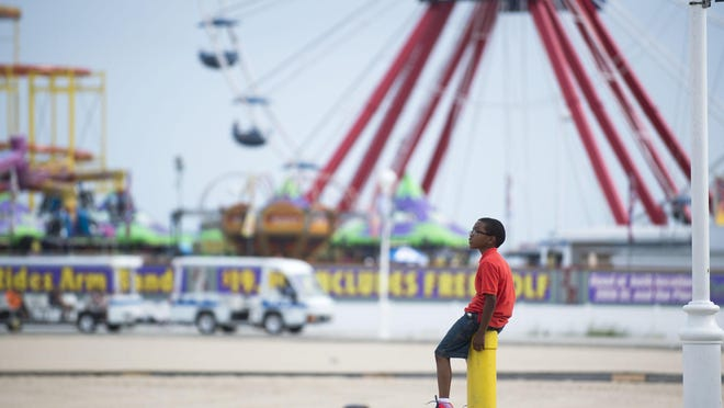 A young boy sits atop a post on a mild afternoon at the Ocean City Boardwalk.