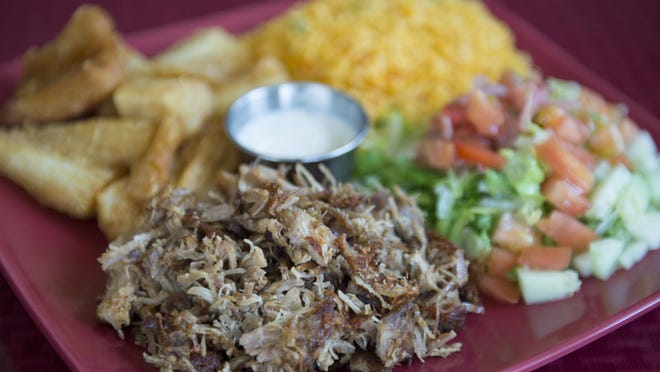 A Pernil dish features shredded pork shoulder, onions, rice, beans and yuca from Los Caballos Locos in Philadelphia.