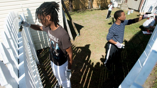 Bennett students Shawn Drummond, 16, left and Terrell Parsons, 17, volunteer to repaint a fence as Salisbury's Promise teams up with Salisbury Urban Ministries to touch up the property as part of Make a Difference Day Saturday in Salisbury.