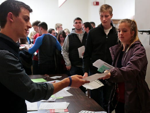 Lisa Greenwood (right), 19, of Ames, hands in her registration