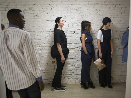 Models line up during rehearsal. Models, wearing clothing