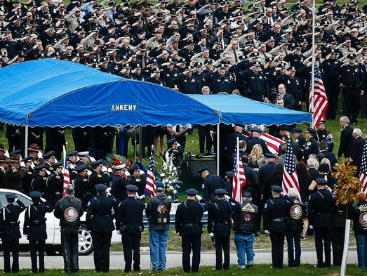 Officers salute as the casket of Des Moines Police