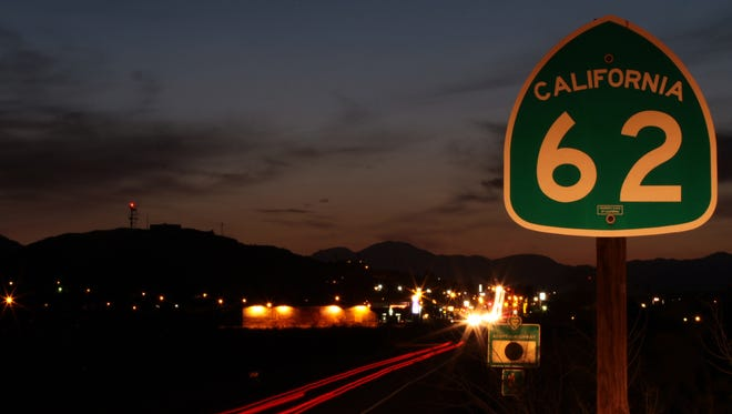 Traffic travels along Highway 62 east of downtown Twentynine Palms, creating streaks of headlights and taillights at sundown on March 11.