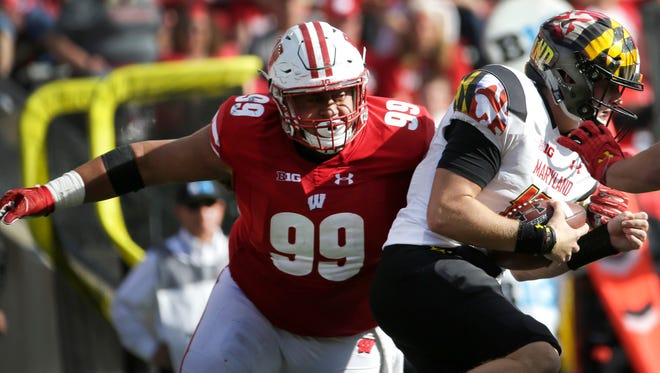 Wisconsin nose tackle Olive Sagapolu pressures Maryland quarterback Max Bortenschlager during a game last season.