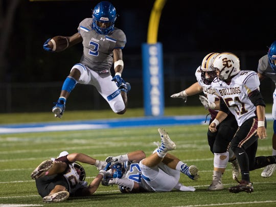 Dana Brown of Barron Collier hurdles over players as he carried the ball in the game against St. Cloud at Barron Collier High Friday night, October 20, 2017.