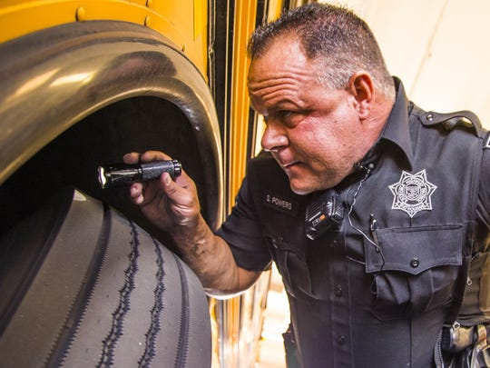 Department of Public Safety Trooper Steve Powers finishes inspecting a Gilbert Public School bus in April.  Arizona school buses failed almost 30 percent of these inspections in 2015, almost double the number from 2013.
