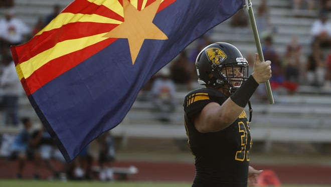 Saguaro's Carson Nugent (33) brings out the Arizona state flag prior to a game at Saguaro High School on August 19, 2016 in Scottsdale.