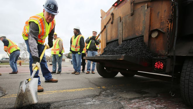 Gov. Rick Snyder assists MDOT workers along Michigan Ave. near Trumbull to patch potholes Thursday, April 23, 2015, in Detroit.