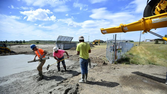 A work crew from Sletten Construction lays concrete the location of the new Lewis and Clark National Forest Service and Bureau of Land Management headquarters on River Drive and 38th Street North on Wednesday.