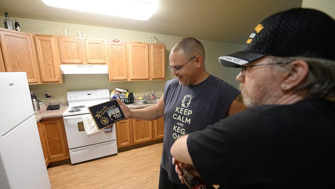 Ed Edict, left, talks with fellow veteran Archie Shaha inside Edict's new Veterans Manor apartment. The apartments were built for low-income veterans.