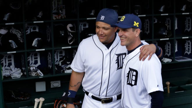 Michigan's head football coach Jim Harbaugh  poses with the Tigers first baseman Miguel Cabrera  in the Tigers dugout before throwing out the first pitch June 30, 2015.