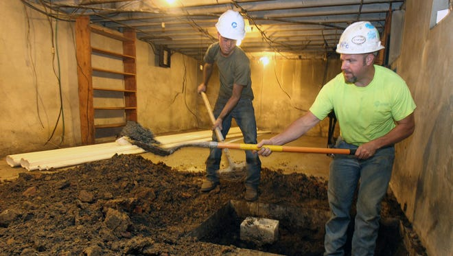 Zac Robinson, left, and Bill Benton of Century Construction Co. dig out an old cast iron sewer for replacement in the basement of the Hellmann Lumber Building in Covington. The nonprofit Center for Great Neighborhoods purchased the 19th century building and is renovating it for use as a west side neighborhood community and arts center.