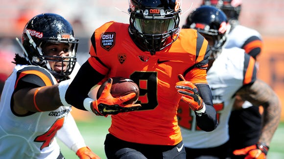 Oregon State's Datrin Guyton runs with the ball up field past linebacker Darrell Songy during the Spring Game inside Reser Stadium, on Saturday, April 18, 2015, in Corvallis.