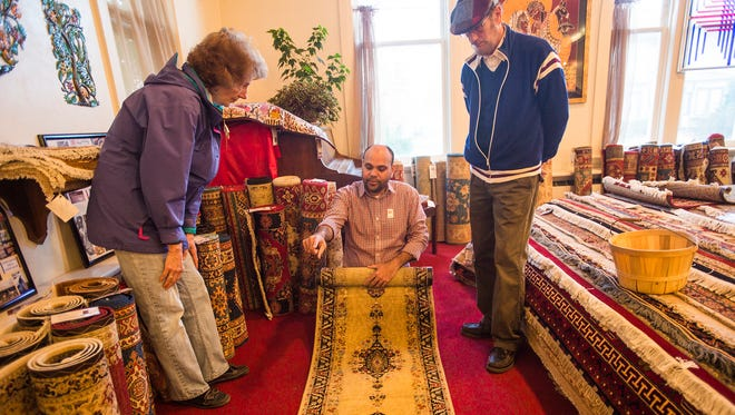 Dottie and Lynn Cairns, right, listen to Ten Thousand Villages sales associate Amir Chaman as he explains differences in handcrafted Pakistani rugs for sale Thursday Nov. 12, 2015 at the 55th annual International Gift and Rug Festival at Fairfield Mennonite Church. The event, originally started by church members, brings international handmade products from 38 different countries to shoppers looking for unique gifts or home decor and gives artisan groups in other countries a chance for fair wages and trade. For the past three years the event has been operated by the Mechanicsburg retail branch of Ten Thousand Villages, one of the largest fair-trade organizations in the world that helps provide international artisan groups with a way to sell their handcrafted products.