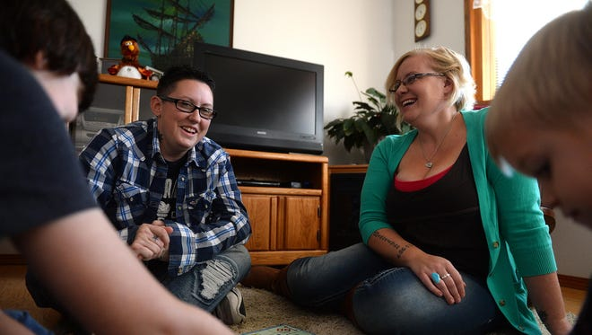 Devon and Noelle Lee play a board game with their children Xander and Gracie on Thursday. The Lees have been married for almost a year since Montana repealed its ban of same-sex marriages.