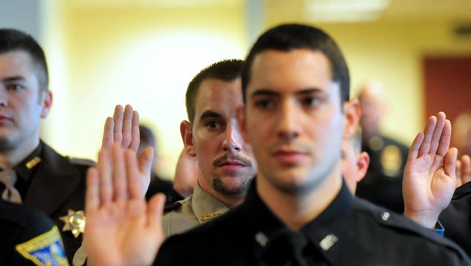Law enforcement officers take their oath of office Friday during the Montana Law Enforcement Academy's graduation ceremony in Helena.