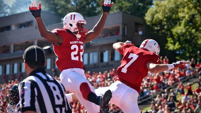 Evan Clark and Dan Harrington celebrate a touchdown for St. John's during the first quarter of the Saturday, Sept. 17, game against St. Olaf at Clemens Stadium in Collegeville.