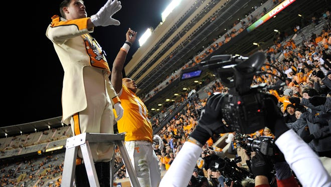 Tennessee quarterback Joshua Dobbs, right, helps to lead the Pride of the Southland marching band with drum major Andrew Vogel after Saturday's 63-37 win over Missouri at Neyland Stadium.