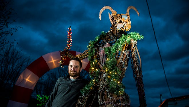 Jeff Asper, artist, metal sculptor and owner of Tossed and Found Art, poses for a portrait at his New Oxford home with his Christmas themed creation - a sculpture of Krampus, a half-goat half-demon figure from traditional German and Alpine folklore who would visit naughty children at Christmas time. Asper said he has been working on the nearly 12 foot tall sculpture for his yard since the spring.