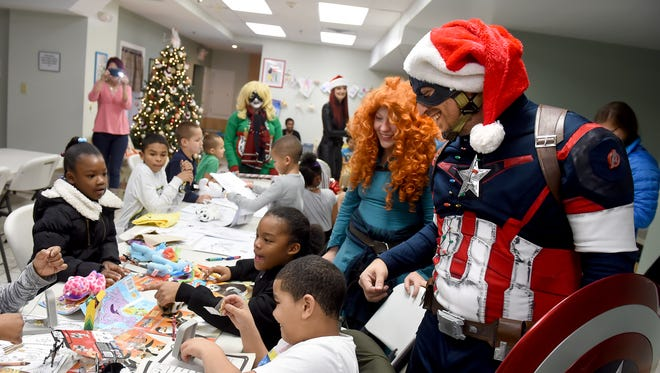"Jason ""Captain America"" Johnson, of the Central Pa. Avengers, talks toys with kids from the LifePath Christian Ministries women and children's shelter. The non-profit group was on hand to hand out gifts and spend time with the children on Saturday, Dec. 10, 2016."