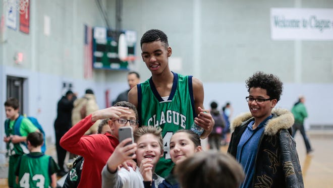 Students crowd around to take a selfie with Clague Middle School 7th-grader Emoni Bates after his team defeated Ann Arbor Steam Middle School on Friday, Feb. 3, 2017 at Clague Middle School in Ann Arbor.
