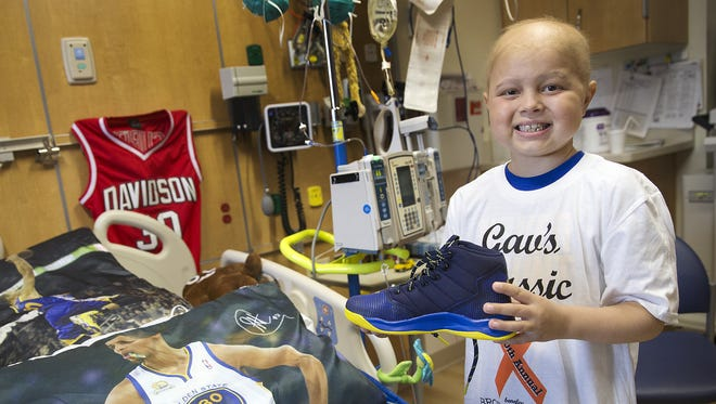 Brody Stephens, 7, poses by his Golden State-themed bed with new Steph Curry basketball shoes at Riley Hospital for Children, Wednesday, July 13, 2016. A friend from Brody's baseball league gave them to him as a gift, since he wouldn't be able to play this season. Stephen is battling leukemia for a second time.