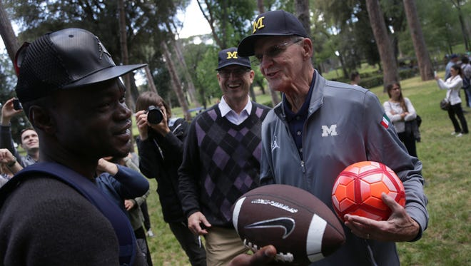 Michigan football coach Jim Harbaugh, center, and his father Jack Harbaugh, right, explain the game of football to Ade, 31 of Nigeria, during a meeting with a group of refugees from the Joel Nafuma Refugee Center at Villa Borghese in Rome on Sunday, April 23, 2017.