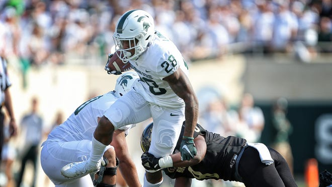 Michigan State running back Madre London (28) is tripped up by Western Michigan linebacker Caleb Bailey (8) during the first half on Saturday, Sept. 9, 2017, in East Lansing.