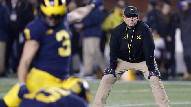 Michigan Wolverines head coach Jim Harbaugh watches place kicker Quinn Nordin (3) warm up before the game against the Minnesota Golden Gophers at Michigan Stadium.