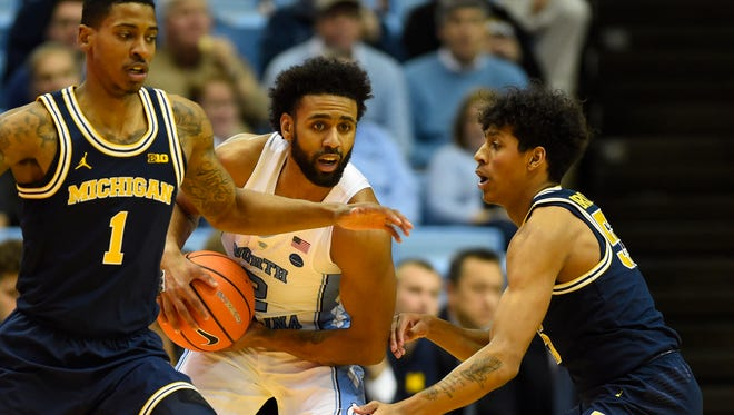 North Carolina guard Joel Berry II (2) with the ball as Michigan guard Charles Matthews (1) and guard Eli Brooks (55) defend in the first half on Wednesday, Nov. 29, 2017, in Chapel Hill, N.C.