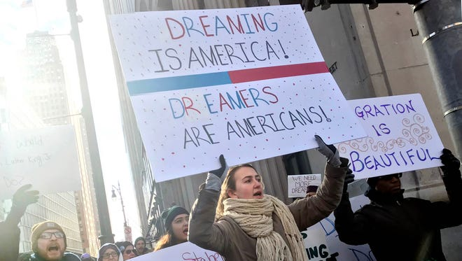 """Fiorela Lesaj of Sterling Heights, center, and other protestors march along Griswold in support of DACA on Wednesday, January 17, 2018, in downtown Detroit. """"No DACA no deal"""" was chanted as they marched."""