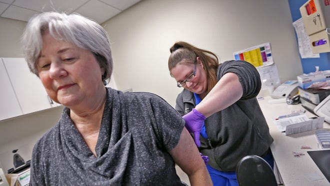 Lynne Corydon, left, receives an allergy shot given by medical assistant Maggon Ray in the Activate Healthcare Heath & Wellness Center at MacAllister Machinery, Wednesday, Feb. 21, 2018.