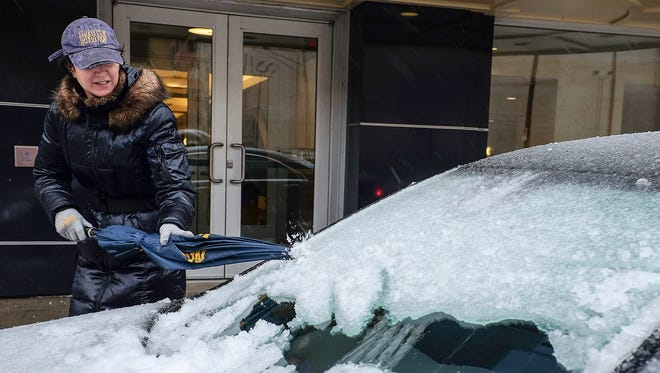 A woman uses an umbrella to chip away at the ice accumulation on her windshield in downtown Lansing, Mich., Sunday, April 15, 2018. Freezing rain that began falling overnight had left roads treacherous and cut power to hundreds of thousands of homes and businesses by midday Sunday in Michigan even as heavy snow was forecast to dump a foot or more of snow on parts of the state's Upper Peninsula by early Monday.