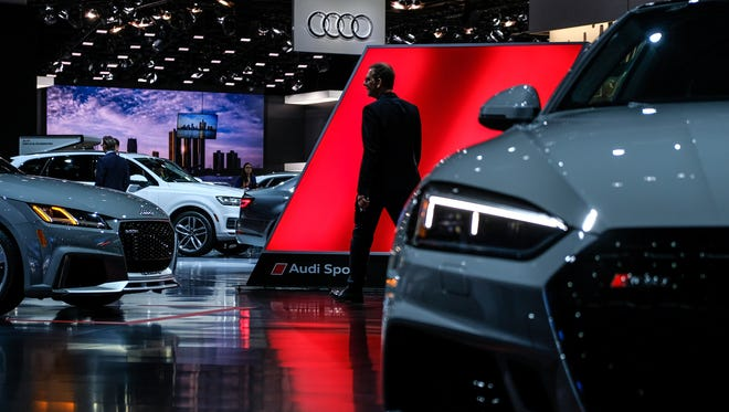 People walk through the Audi display on Monday, Jan. 15, 2018 during the 2018 North American International Auto Show at Cobo Center in Detroit.