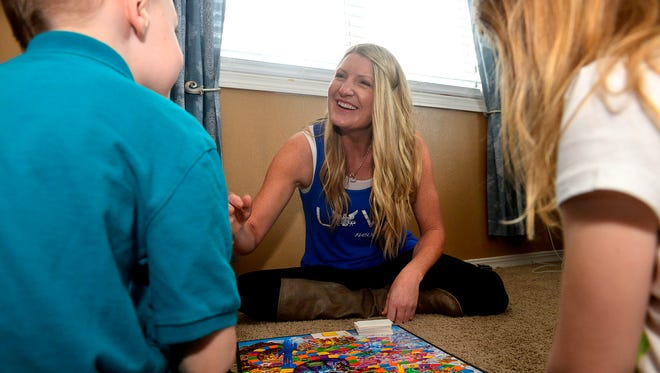 Robynn Dunn plays a game with her children earlier this week. Cascade County Sheriff's Deputy Joe Dunn was killed in the line of duty last year, and Robynn would like to thank all those who showed support for her family after her husband's death.