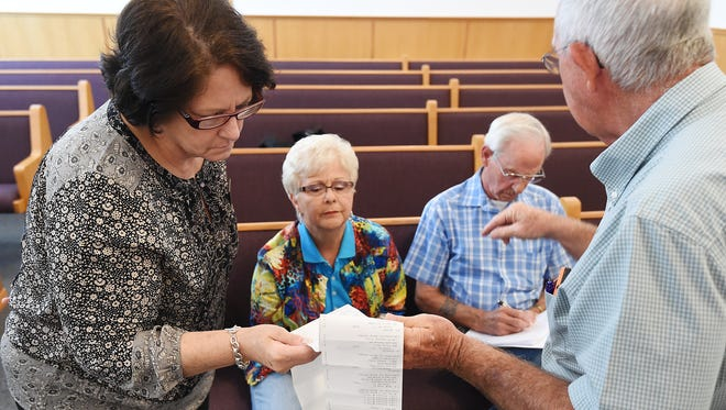 Willa Mae Tilley (left), Democratic candidate for State Representative District 100, and Nelda Speaks (center), Republican candidate for the same seat, listen Thursday as Baxter County Election Commission chairman Bob Bodenhamer (right) details a mistake in the electronic ballots for three precincts in which the State Representative District 100 race was left off.