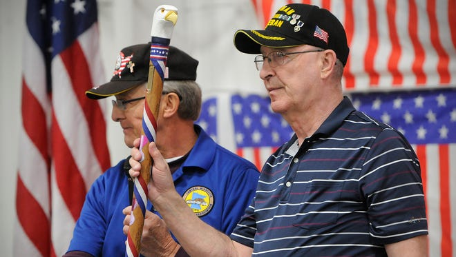 Central Minnesota Woodcarvers Association President Curt Hutchens, left, presents Vietnam veteran Tom Wainright, of Sartell, with an Honor Cane during a ceremony Saturday at Sports Arena East in Sauk Rapids. A hand-carved cane was also presented to veteran Bob Larson during the event.