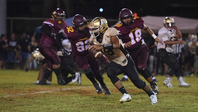 Tiyan Titans quarterback Kobe Quimbao (13) runs the ball against the Father Duenas Friars during their Interscholastic Football League game at Hal's Angels Field on Sept. 2, 2017.