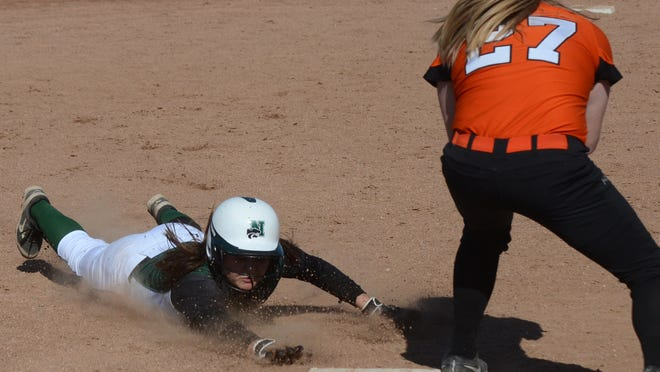 Novi's Nicole Ireland (left) slides into third base ahead of tag by the Mustangs' Brianna Nayh during the first game of their doubleheader.
