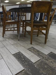 Broken floor tiles with no grout cover the student library at Simon Sanchez High School in Yigo on Oct. 1.