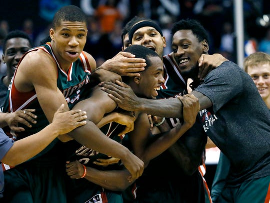 Milwaukee Bucks' Khris Middleton is embraced by teammates after making the game-winning basket against the Suns' after an NBA basketball game, Monday, Dec. 15, 2014, in Phoenix. The Bucks won 96-94.