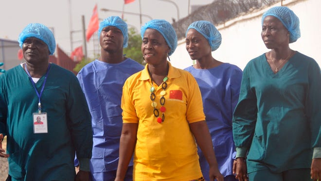 Ebola patient Beatrice Yardolo, center, leaves the Chinese Ebola treatment center were she was treated, surrounded by Ebola health workers on the outskirts of Monrovia, Liberia, March 5, 2015.