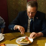 GOP Presidential Candidate John Kasich eats a piece of pizza at Gino's Pizzeria and Restaurant on March 30, 2016, in the Queens borough of New York City.