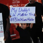 Isaiah Whitlock, middle, holds up a sign during a Black Lives Matter protest in Sparks on July 22, 2016.