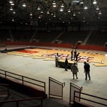 Workers lay the UL basketball court down at Blackham Coliseum on Tuesday. The coliseum will be used for the Cajuns basketball game Thursday against Evansville in the CollegeInsider.com Tournament quarterfinals.