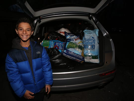 Ethan Swartz shows off the donations he collected for