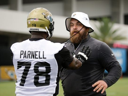 Jacksonville Jaguars tackle Jermey Parnell (78) goes through a drill with assistant offensive line coach Luke Butkus during practice at NFL football training camp, Saturday, Aug. 1, 2015, in Jacksonville, Fla. (AP Photo/John Raoux)
